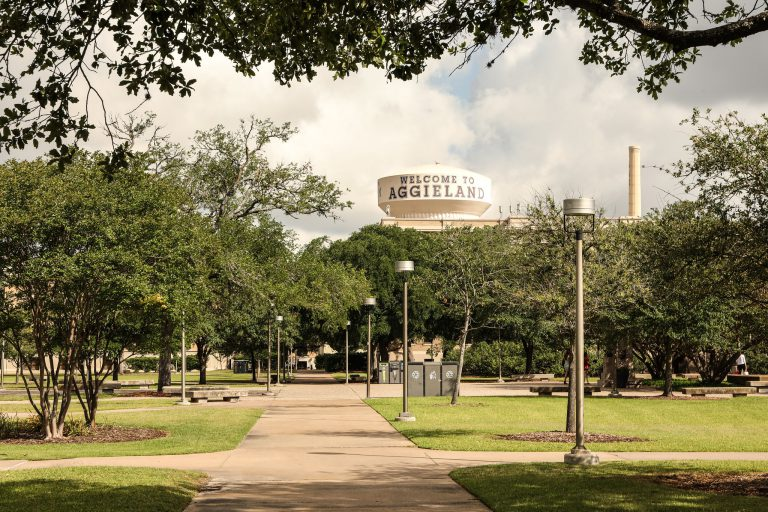 """Wide shot on Academic Plaza with the """"Welcome to Aggieland"""" water tower in the background."""