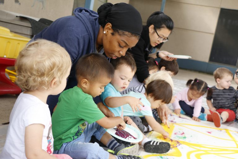 Teacher assisting a group of young children paint.