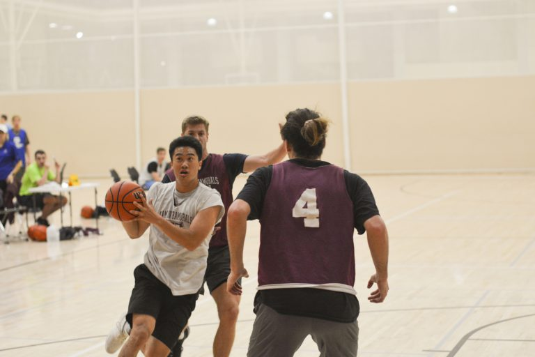 A group of students playing indoor basketball at the Rec Center.