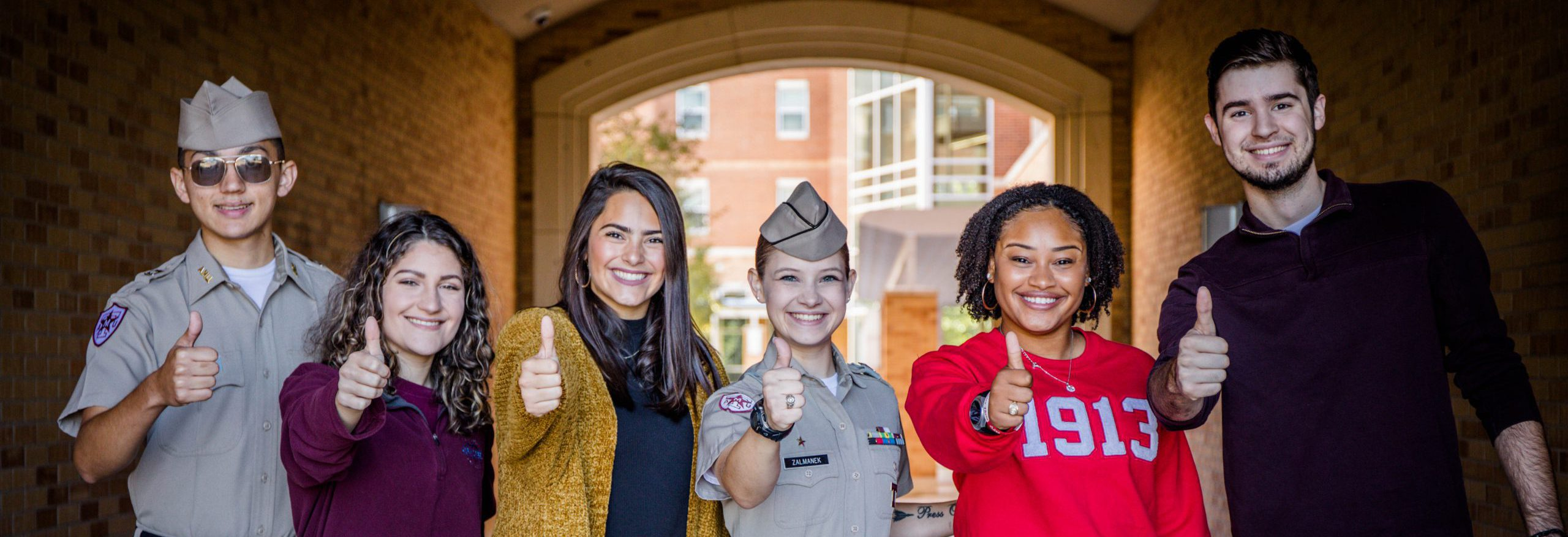 Five Aggie students of different backgrounds showing the Gig' Em sign.