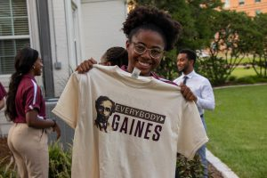 "Image of a female student holding up a t-shirt that reads ""Everybody Gaines"""