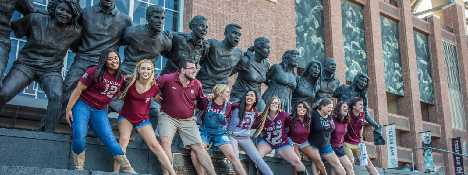 Ten Aggie Students Sawing them off in front of the War Hymn statue in front of Kyle Field