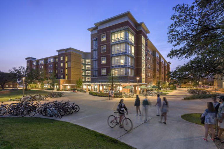 An image of Hullabaloo at night with students walking on the sidewalk.