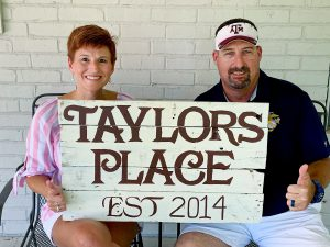 "Image of Tanya and T.J. Gillespie holding a sign that reads ""Taylors Place, Est 2014"""