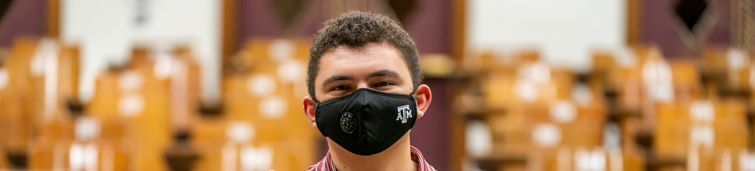 student facing the camera wearing a mask