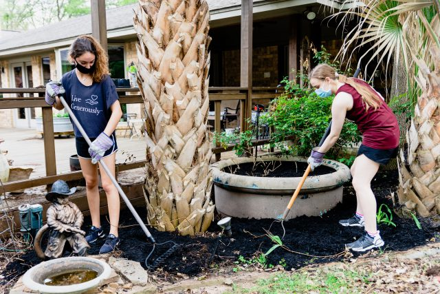 Image of two students wearing face coverings while raking and cleaning up an outdoor area.