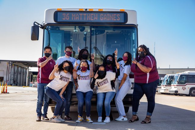 Image of the Matthew Gaines Society in front of an Aggie Spirit Bus displaying the newly named Matthew Gaines route on the bus marquee.