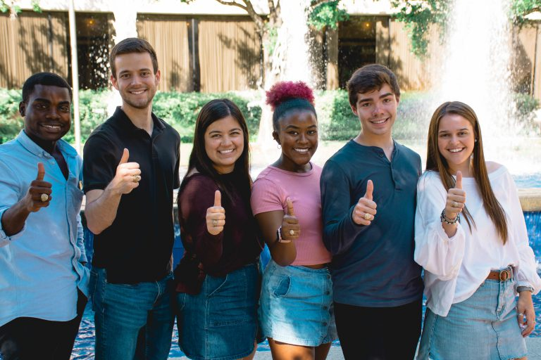 Image of six students with their Aggie ring throwing a gig 'em