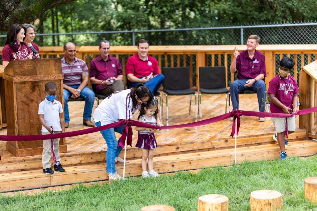 Students at the Becky Gates Children's Center use safety scissors to cut the ribbon during the ceremony celebrating the new nature playground